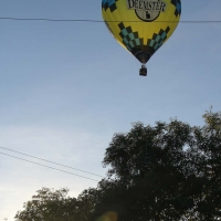 Hot air balloon taking off from across the road
